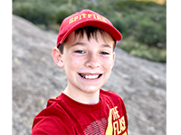 (Thumbnail of a boy in a red hat, smiling at camera)